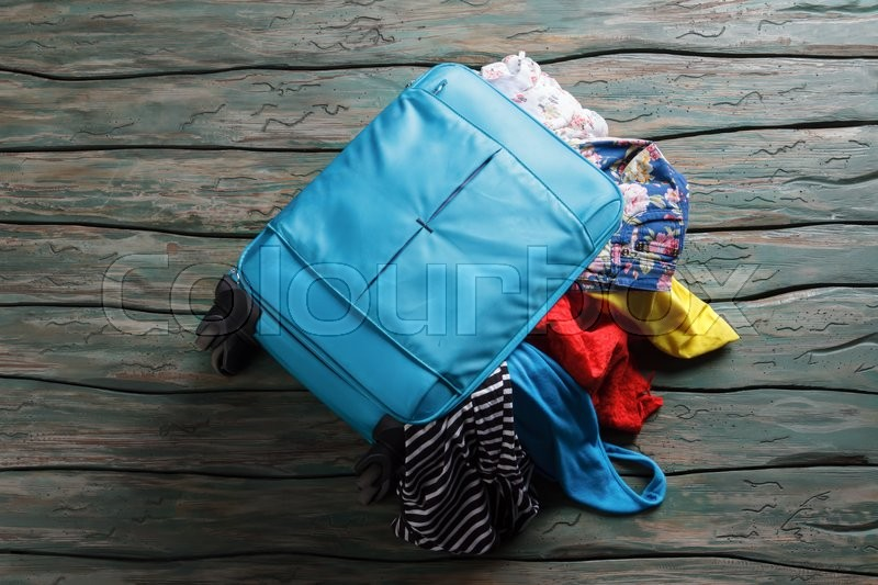 Stock image of 'Luggage bag filled with clothes. Things fall out of suitcase. Summer essentials only. Packing bag and making mess.'