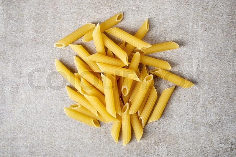 Stock image of 'Penne pasta on stone table, from above'
