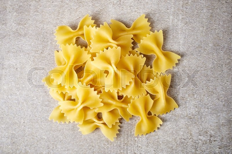 Stock image of 'Bow tie pasta on stone table, from above'