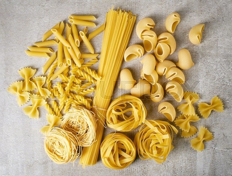 Stock image of 'Various types of pasta on stone table, from above'