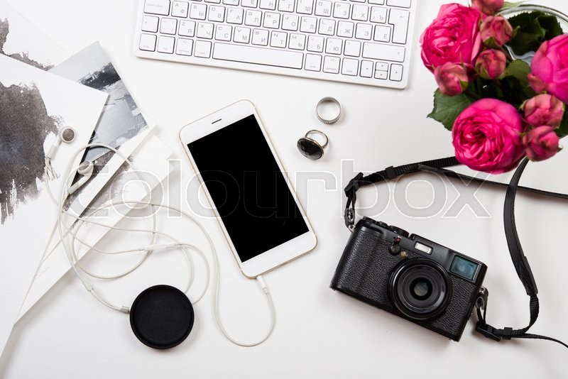 Stock image of 'Modern smartphone, computer keyboard, pink flowers and photo camera on white table, freelancer girl's workspace'