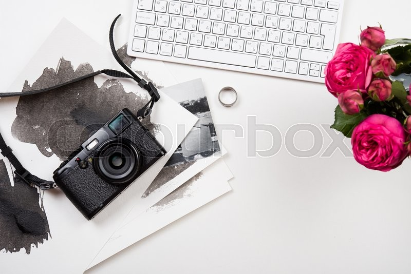 Stock image of 'Modern computer keyboard, pink flowers and photo camera on white table, photographer girl's workspace'