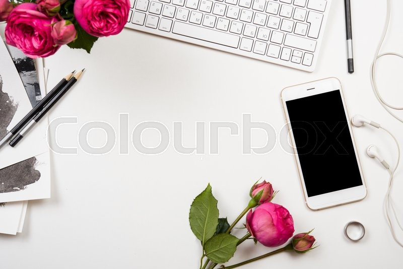 Stock image of 'Modern smartphone, computer keyboard and fesh pink flowers on white table, freelancer blogger workspace, screen mockup'