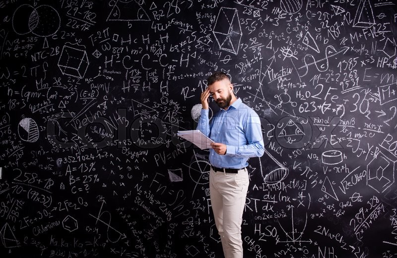 Stock image of 'Hipster teacher with notebook against big blackboard with mathematical symbols and formulas. Studio shot on black background.'