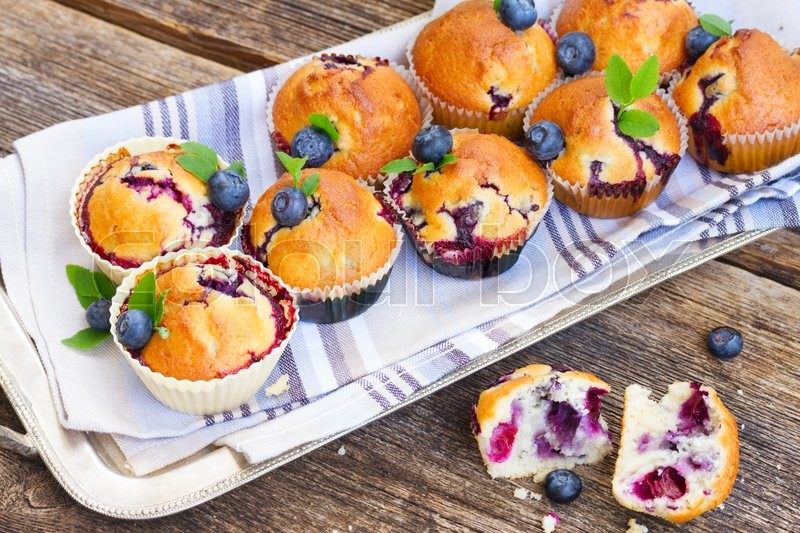 Stock image of 'cplate of upcakes with fresh blueberry berry and leaves on wooden table'