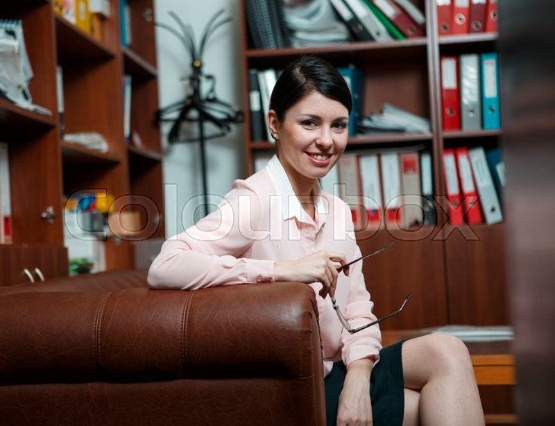 Stock image of 'Business woman rests at leather sofa'