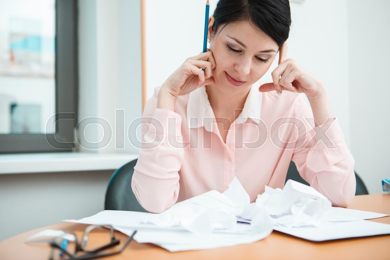 Stock image of 'Businesswoman sitting at desk in the office in thoughts.'