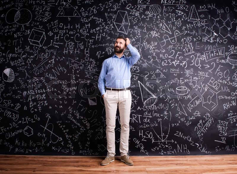 Stock image of 'Hipster teacher scratching head, standing against big blackboard with mathematical symbols and formulas. Studio shot on black background.'