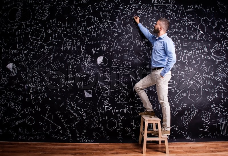 Stock image of 'Hipster teacher writing on big blackboard with mathematical symbols and formulas, standing on step ladder. Studio shot on black background.'