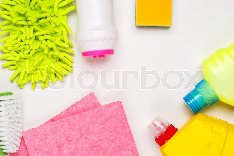 Stock image of 'House cleaning products on white table. Top view with empty space in center for text or logo.'
