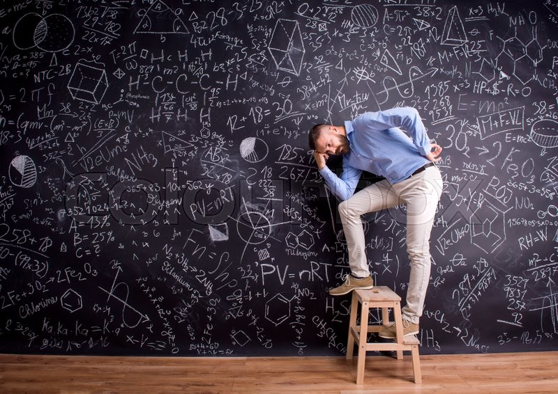 Stock image of 'Hipster teacher standing on step ladder, against big blackboard with mathematical symbols and formulas. Studio shot on black background.'