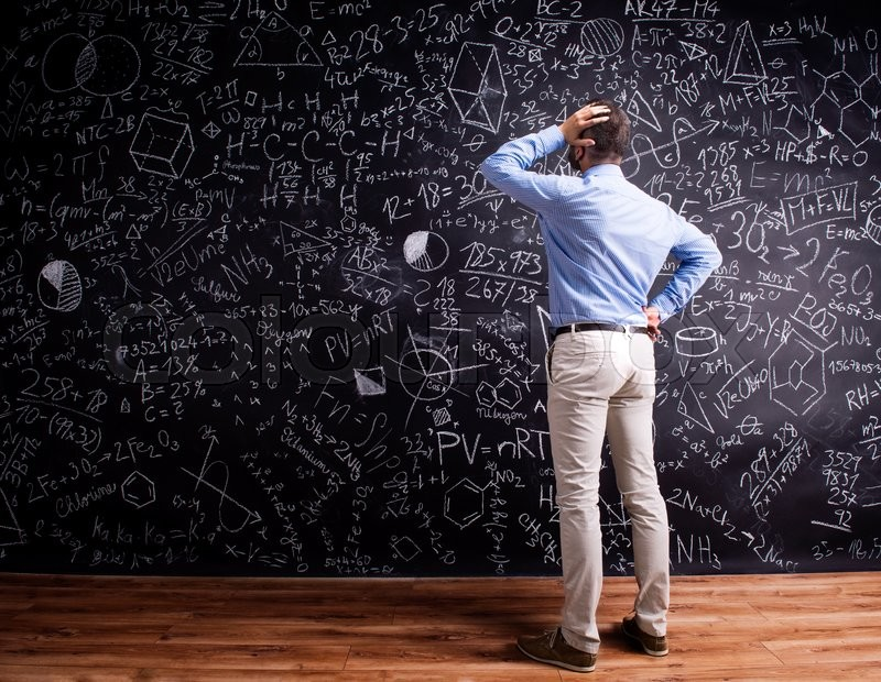 Stock image of 'Hipster teacher scratching head, standing against big blackboard with mathematical symbols and formulas. Studio shot on black background. Rear view.'