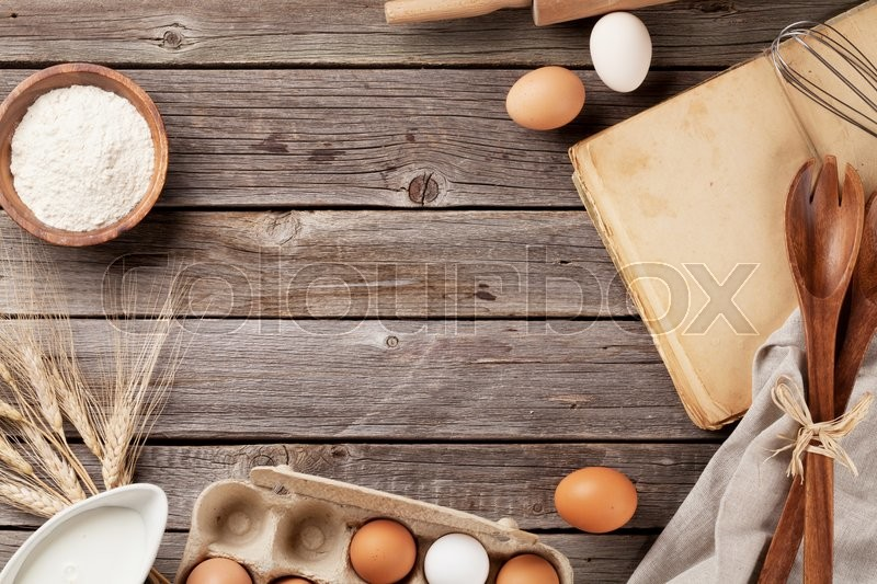 Stock image of 'Kitchen table with cookbook, utensils and ingredients. Top view with copy space'
