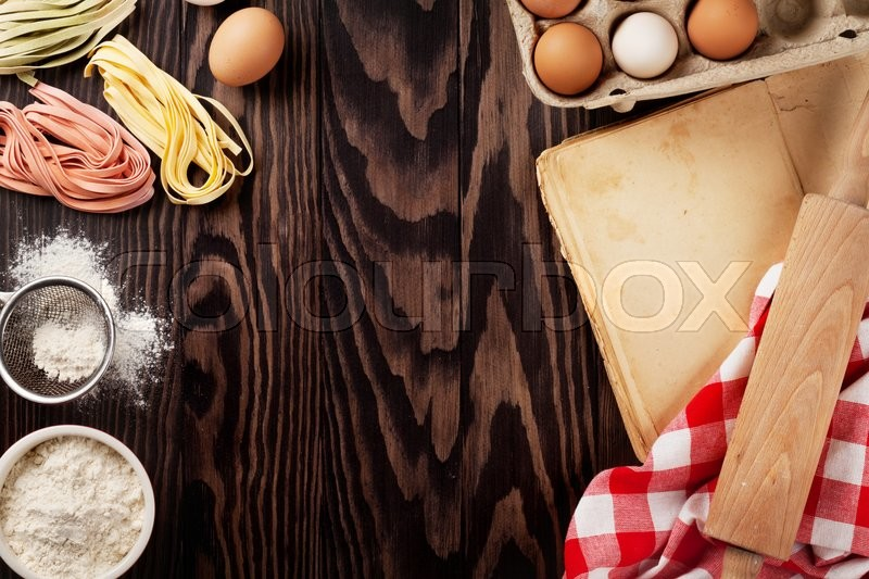 Stock image of 'Homemade pasta cooking, utensils and vintage cooking book on wooden table. Top view with copy space'