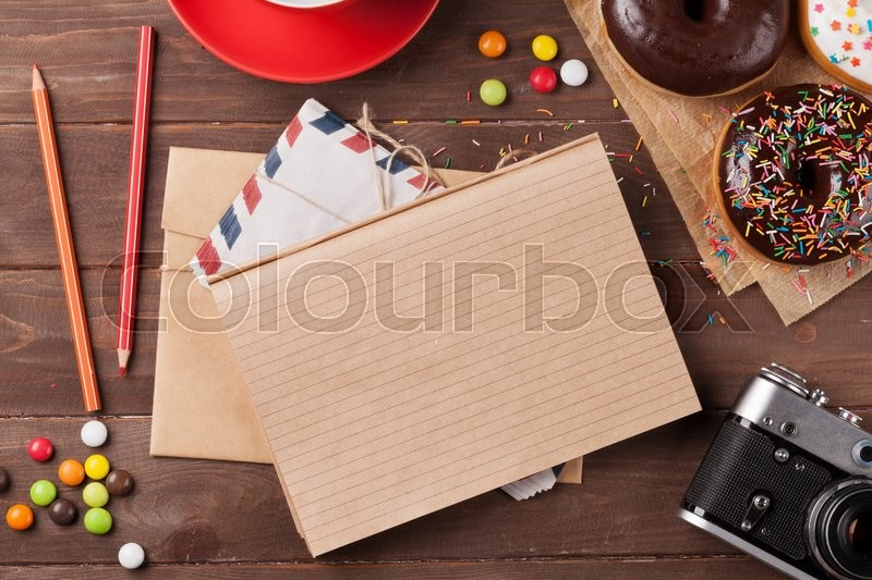 Stock image of 'Notepad, donuts and coffee on wooden table. Top view with copy space'