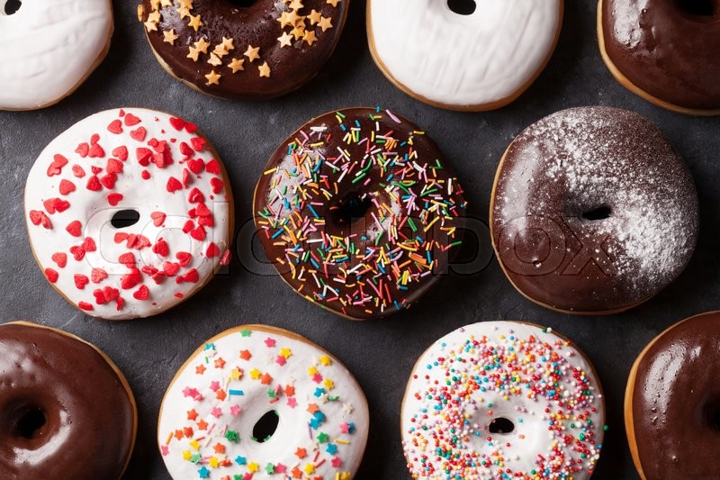 Stock image of 'Colorful donuts on stone table. Top view'