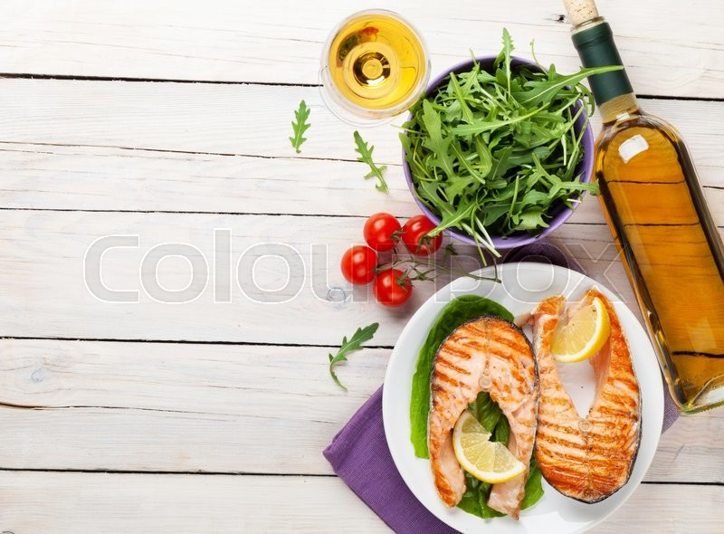 Stock image of 'Grilled salmon and white wine on wooden table. Top view with copy space'