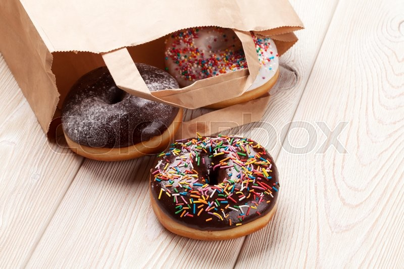 Stock image of 'Colorful donuts bag on wooden table'