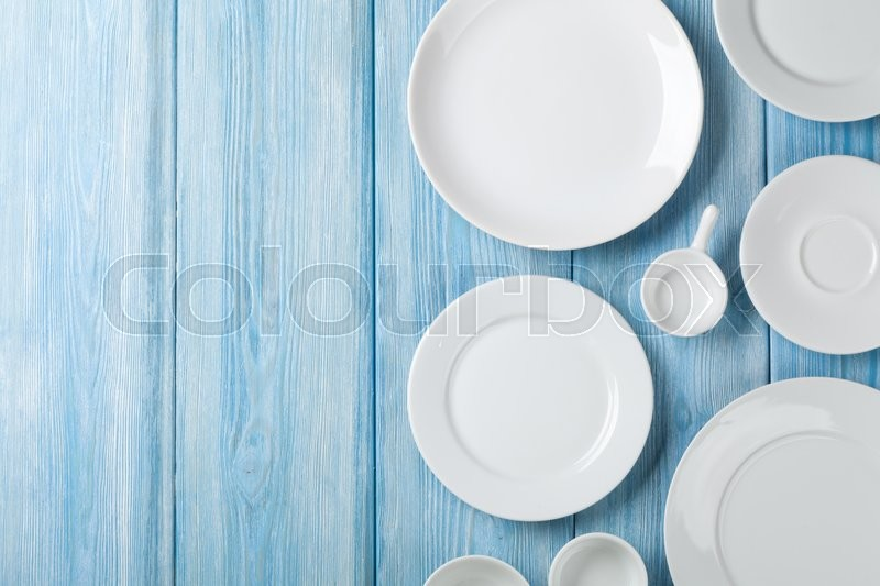 Stock image of 'Empty plates and bowls on blue wooden background. Top view with copy space'