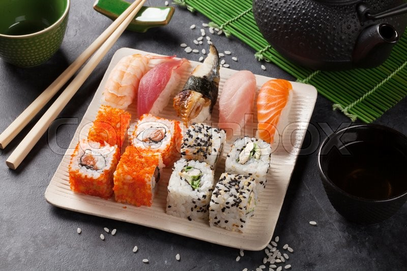 Stock image of 'Set of sushi, maki and green tea on stone table'