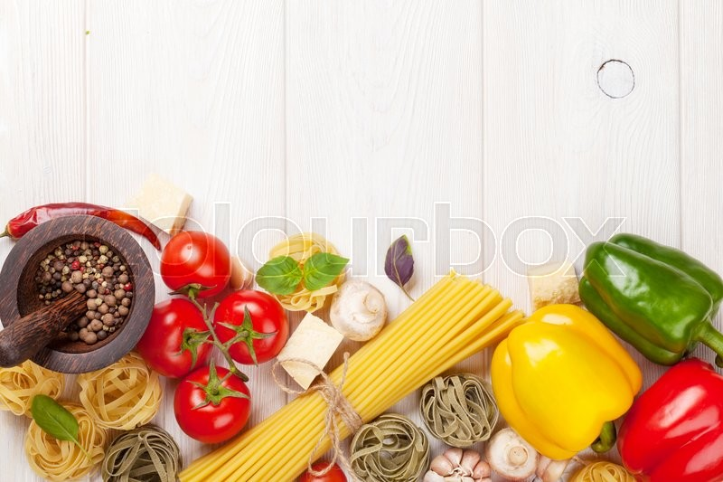 Stock image of 'Italian food cooking ingredients. Pasta, tomatoes, peppers. Top view with copy space'