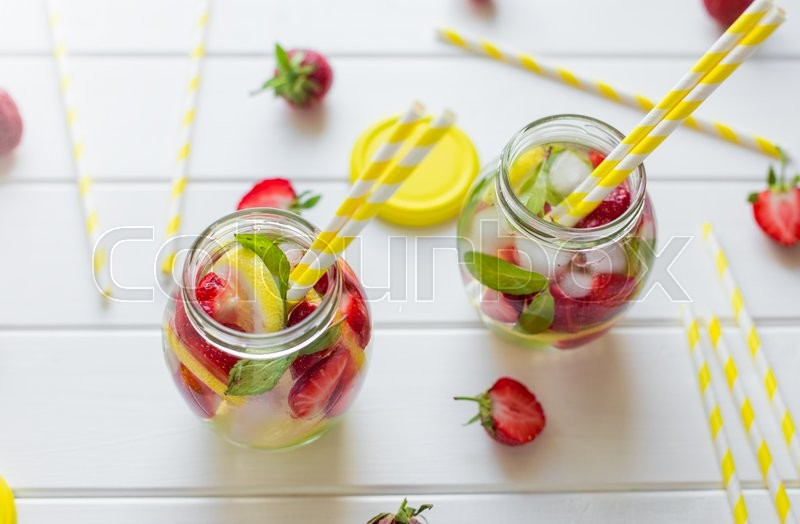 Stock image of 'Two glasses withcocktail tubes. homemade strawberry lemonade, served with fresh strawberries, mint, lime and ice cubes'
