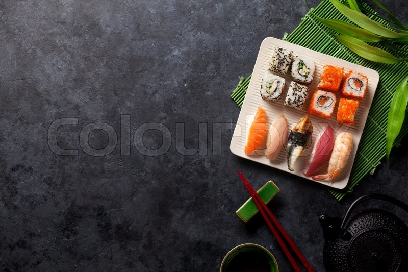 Stock image of 'Set of sushi, maki and green tea on stone table. Top view with copy space'