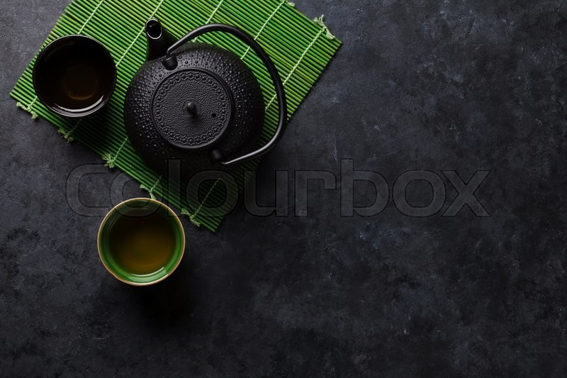 Stock image of 'Green tea cups and teapot on stone table. Top view with copy space'