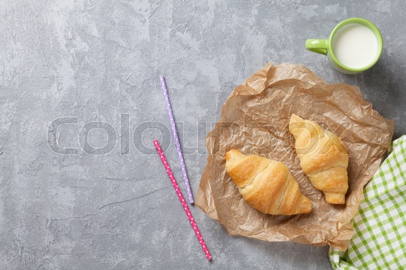 Stock image of 'Fresh croissants and milk on stone table. Top view with copy space'