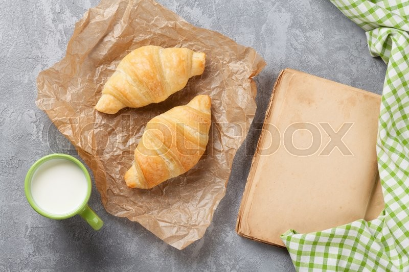 Stock image of 'Fresh croissants, milk and old book on stone table. Top view with copy space'