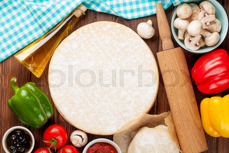Stock image of 'Pizza cooking ingredients. Dough, vegetables and spices. Top view with copy space'