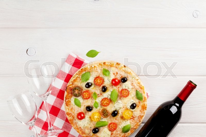Stock image of 'Italian pizza with cheese, tomatoes, olives, basil and red wine on wooden table. Top view with copy space'