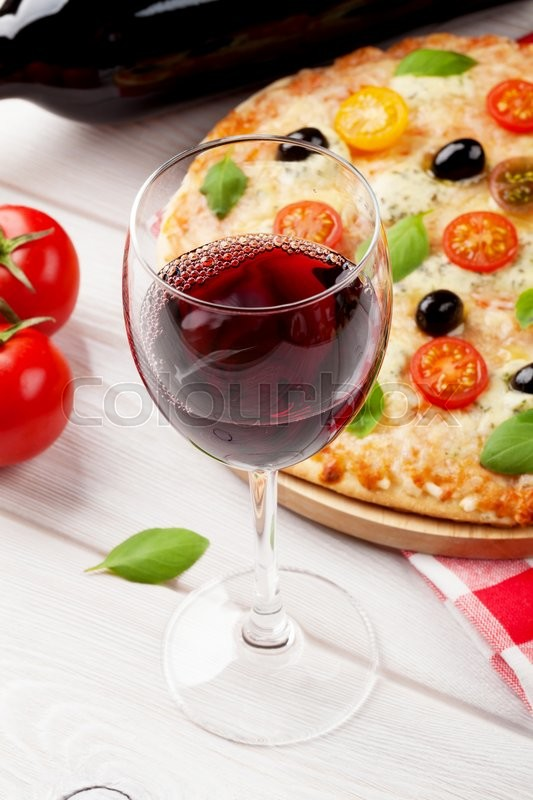 Stock image of 'Glass of red wine and italian pizza with cheese, tomatoes, olives and basil'