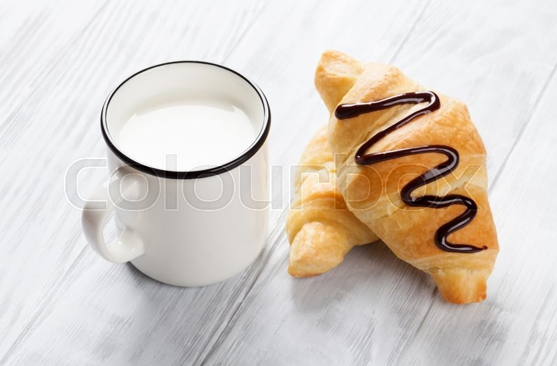 Stock image of 'Fresh croissants and milk on wooden table'