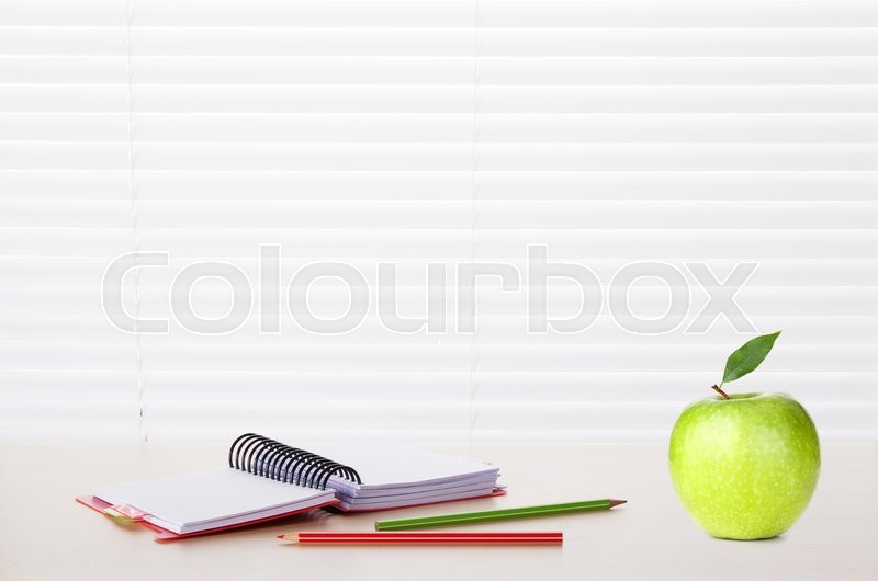 Stock image of 'Office workplace with supplies and apple on wood desk table in front of window with blinds. View with copy space'