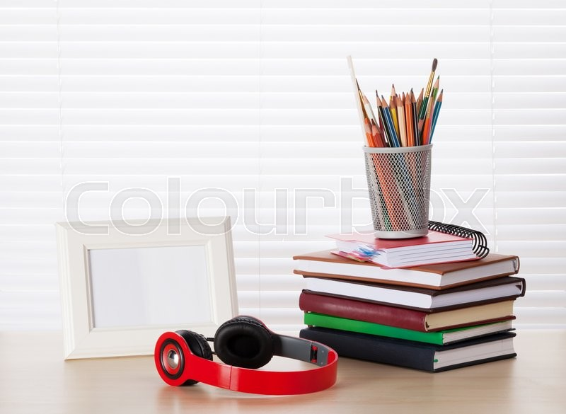 Stock image of 'Office workplace with photo frame, headphones, books and pencils on wood desk table in front of window with blinds'