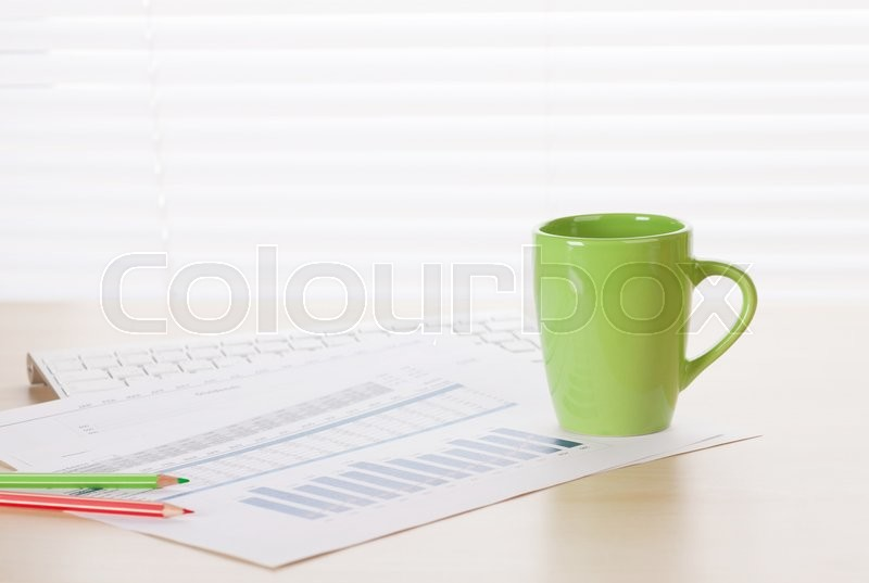 Stock image of 'Office workplace with supplies and reports on wood desk table in front of window with blinds'