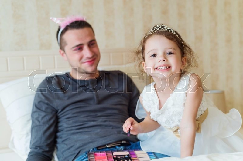 Stock image of 'Cute little girl in princess dress putting on colorful make up on her father'