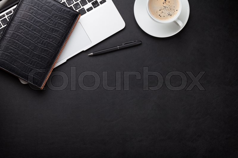 Stock image of 'Office leather desk workplace table with laptop, coffee cup, notepad and pen. Top view with copy space'