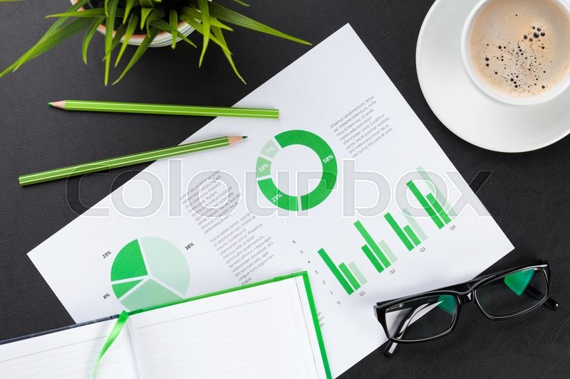 Stock image of 'Office desk workplace with charts, coffee cup, plant and notepad on leather table. Top view'