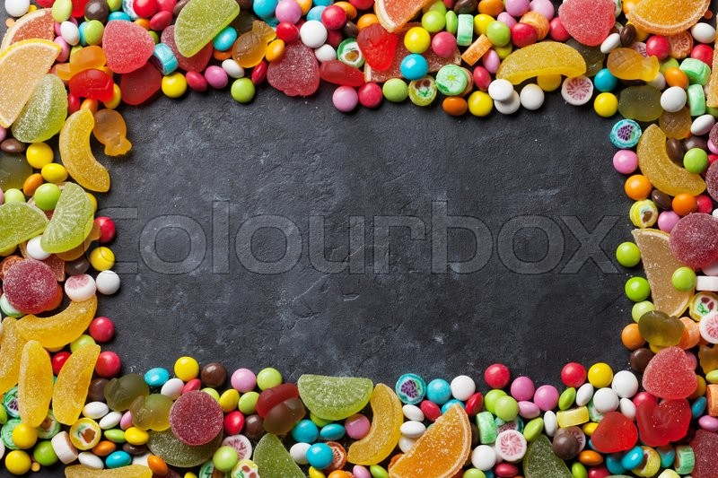 Stock image of 'Colorful candies, jelly and marmalade frame over stone background. Top view with copy space'