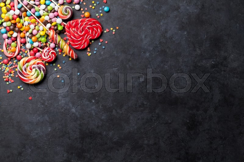 Stock image of 'Colorful candies and lollipops over stone background. Top view with copy space'