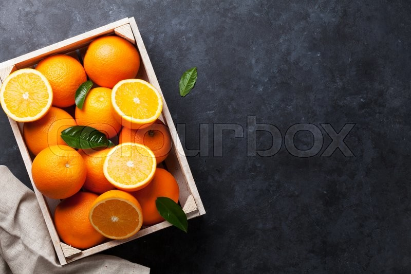 Stock image of 'Fresh orange fruits in wooden box on stone table. Top view with copy space'