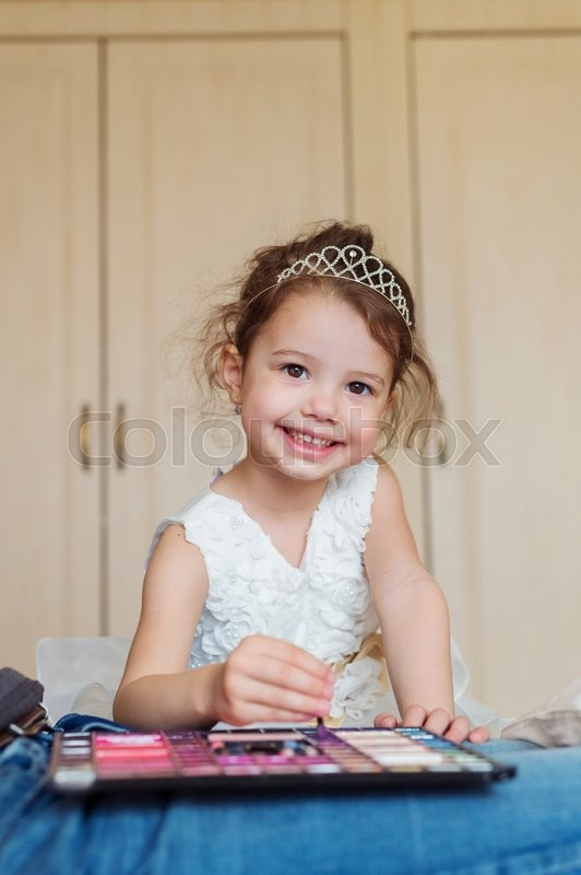 Stock image of 'Cute little girl with princess crown smiling, playing with make up'