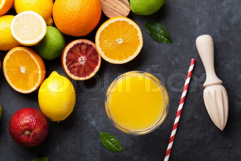 Stock image of 'Fresh ripe citruses and juice. Lemons, limes and oranges on dark stone background. Top view'