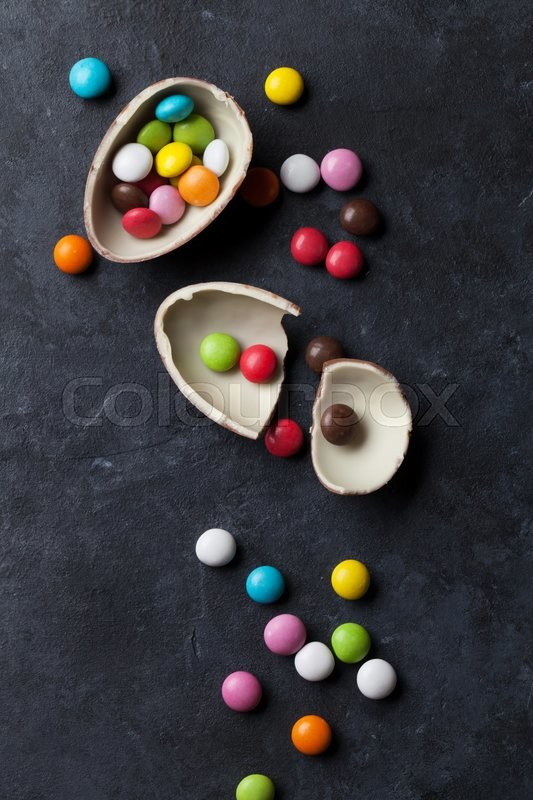 Stock image of 'Colorful candies and chocolate egg on stone background. Top view'
