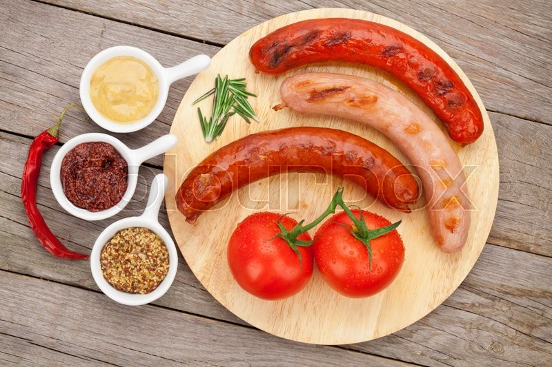 Stock image of 'Various grilled sausages with condiments and tomatoes on cutting board'