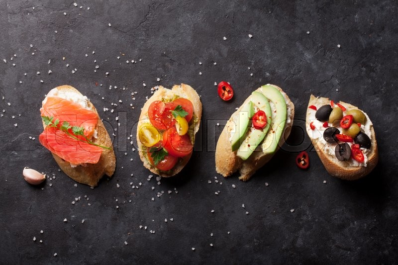 Stock image of 'Toast sandwiches with avocado, tomatoes, salmon and olives on stone background. Top view'