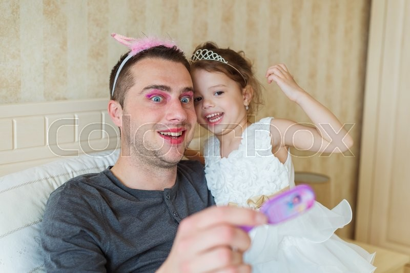 Stock image of 'Cute little girl in princess dress that put on colorful make up on her father'
