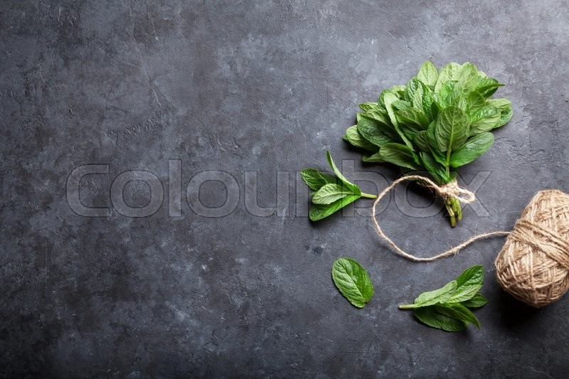 Stock image of 'Fresh mint leaves herb on stone table. Top view with copy space'